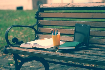 A photo of a wooden park with an open book, a small laptop, a closed green book, and a yellow cup of colored pencils and pens.